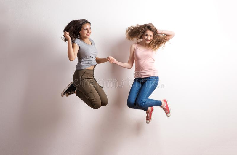 Two young beautiful women in studio, jumping. stock image