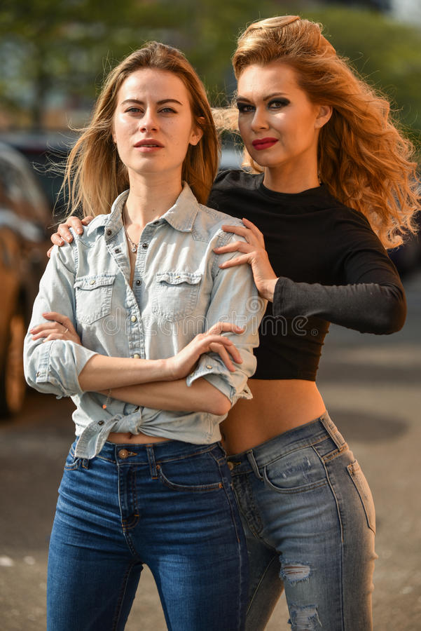 Two young beautiful women in stylish outfits posing on the street. stock image