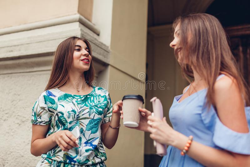 Two young beautiful women talking drinking coffee. Girls having fun in city. Best friends chat outdoors royalty free stock photos