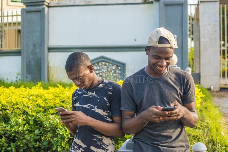 two young black men using their mobile phones outdoor, texting, and browsing the internet, smiling while using their phones stock image