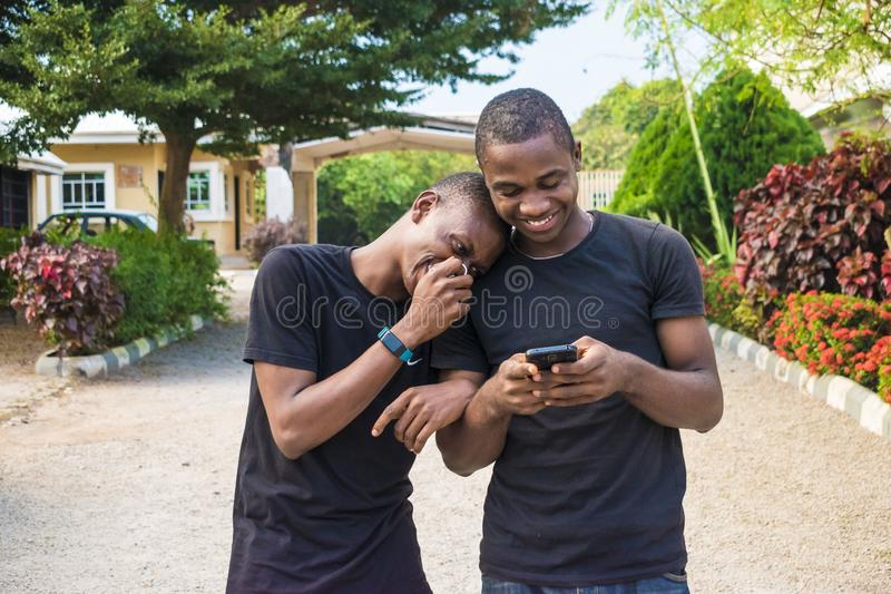 two young black men walking and holding each other laughing together while viewing content on a mobile phone. gay couple laughing royalty free stock image