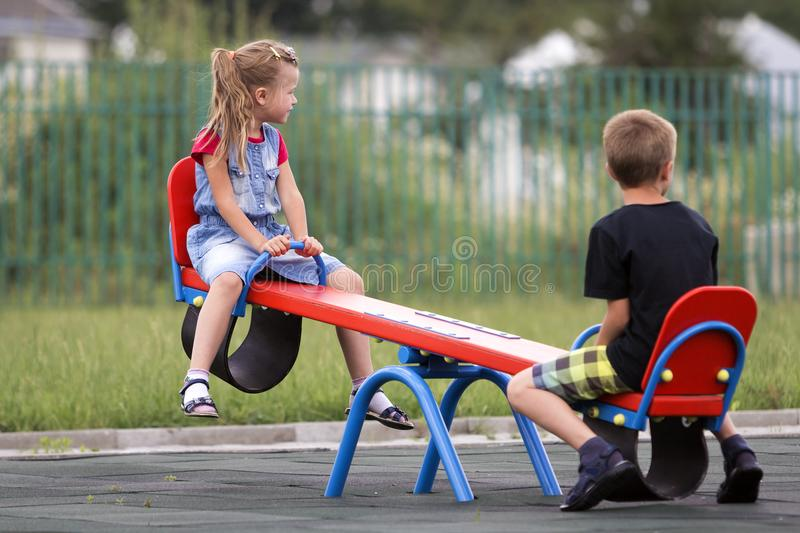Two young blond children preschooler girl with long ponytail and cute school boy swing on see- saw on bright green blurred backgro stock images