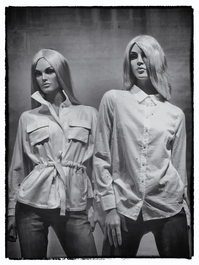 two young blonde female mannequins wearing white shirts and jeans royalty free stock photos