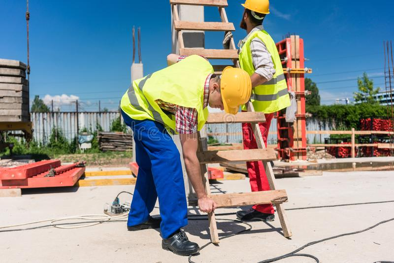 Two young blue-collar workers leaning a ladder royalty free stock photo