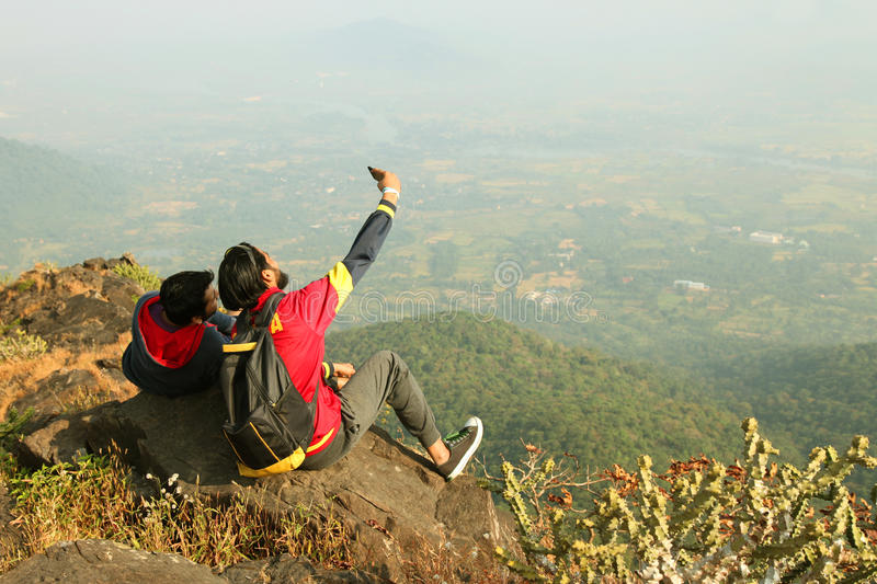 Two Young boys with backpack taking Selfie on the top of a mountain and enjoying valley view stock photo