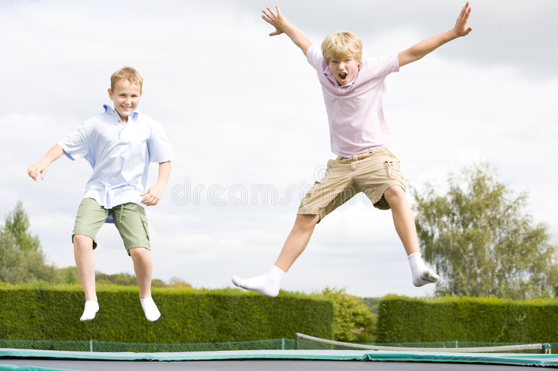 Two young boys jumping on trampoline smiling. At camera royalty free stock photos