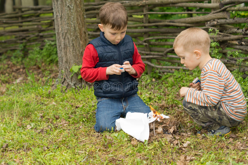 Two young boys lighting a fire outdoors. As they play together in a garden or park squatting down in the grass setting fire to leaves, twigs and paper royalty free stock images