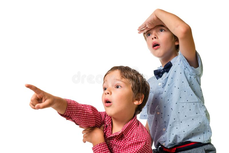 Two young boys looking ahead, surprised, pointing finger to unknown object stock photos