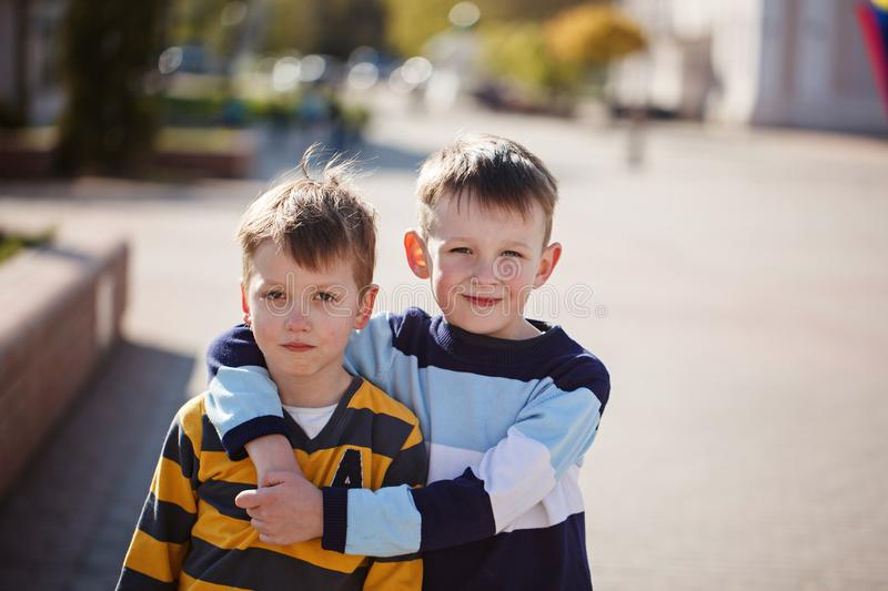 Two young boys outdoors smiling and laugh. Concept friendship stock images