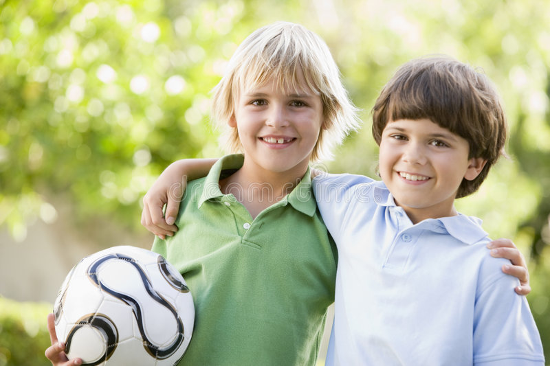 Two young boys outdoors with soccer ball smiling stock photography