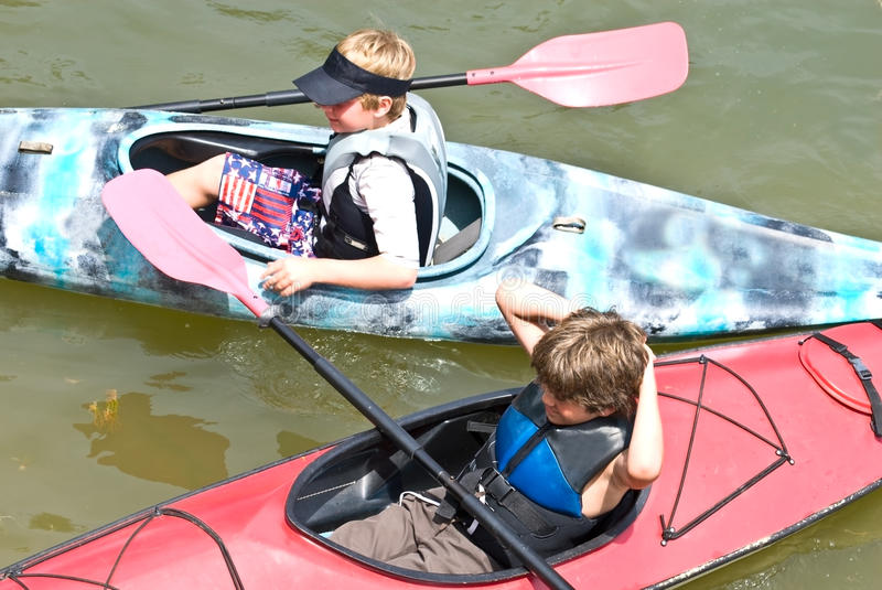 Two Young Boys Ready to Kayak. Two young boys in kayaks getting ready to go out together. 9 and 10 years old stock photography