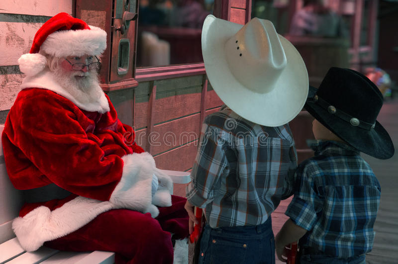 Two young buckaroo kids talk things over with Santa. Two little cowboys in Western clothing talk with Santa Claus before Christmas stock photos
