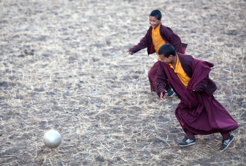 Two young buddhist monk playing soccer stock photos