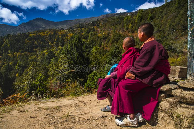 Two young Buddhist novice monks sit in mountain and see the peak , Phajoding monastery , Bhutan royalty free stock photography