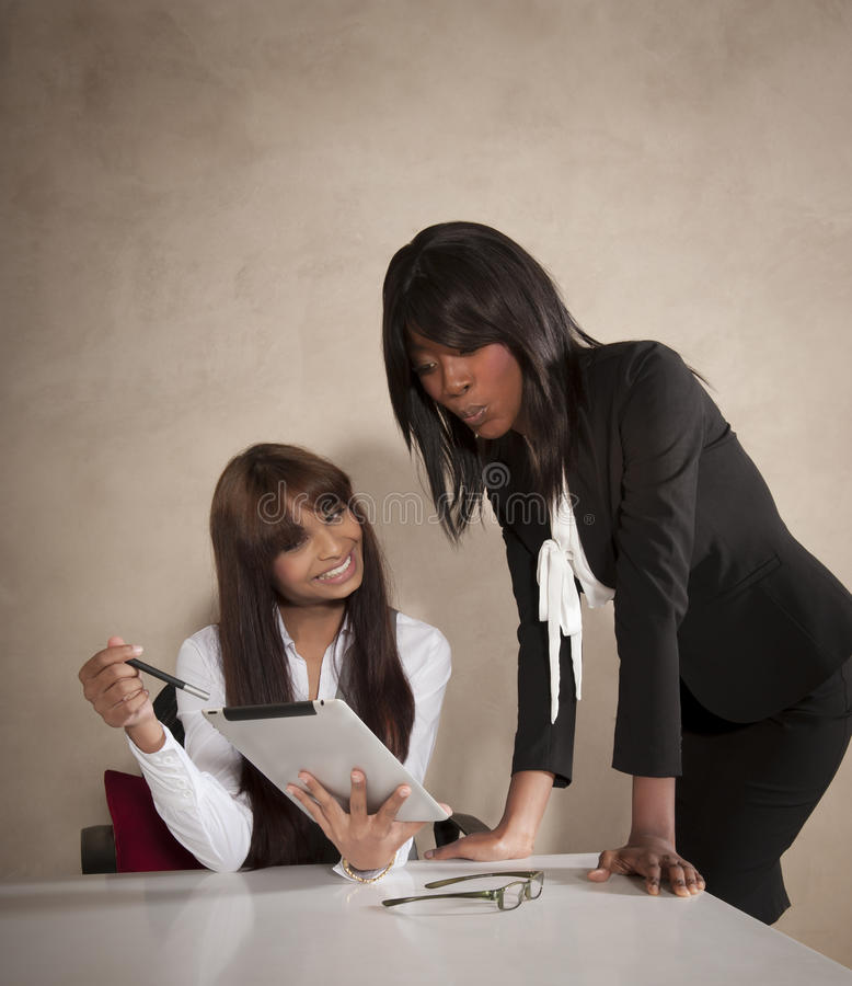 Two Young Business Executives Working At Desk Royalty Free Stock Photos
