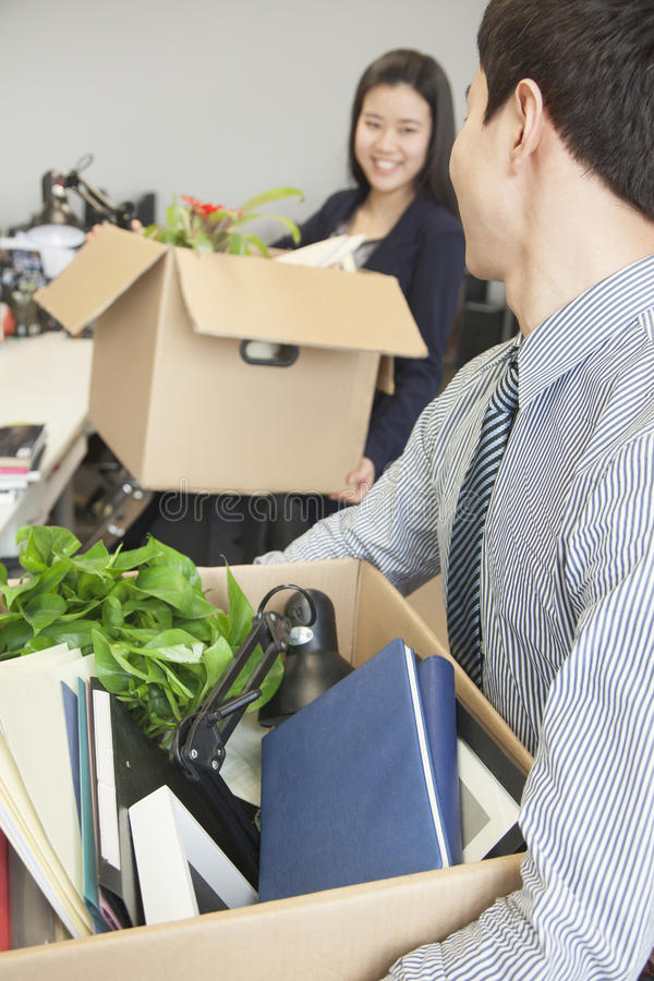 Two young business people carrying boxes with office items royalty free stock photography