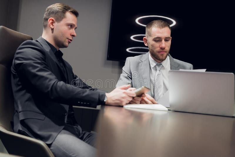 Two young business people discussing work during a business presentation in conference room stock image
