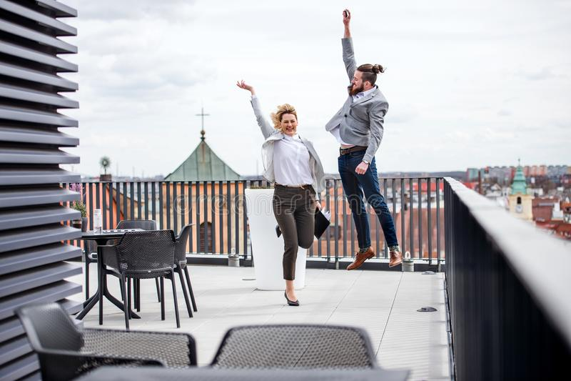 Two young business people jumping on terrace outside office, expressing excitement. Two young business people jumping on a terrace outside office, expressing stock photo