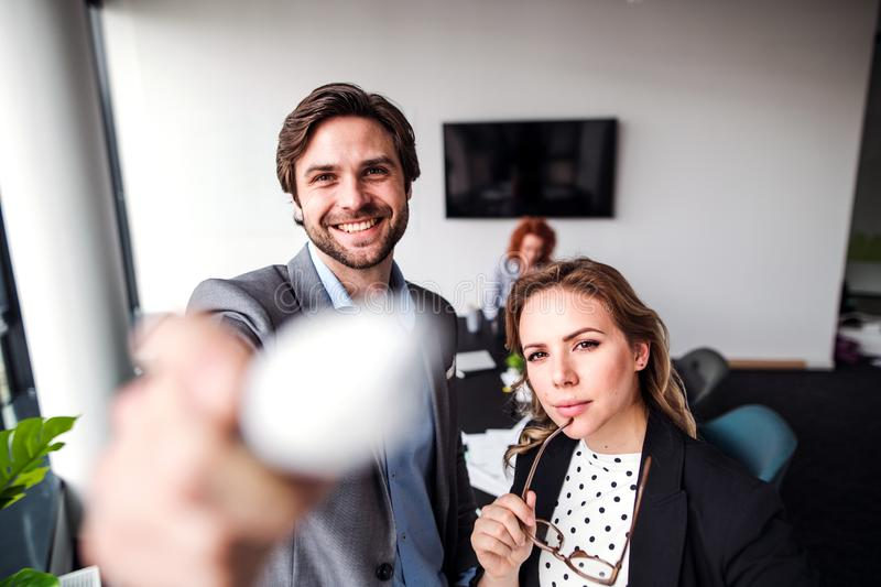 Two young business people in an office, looking at camera. stock photos