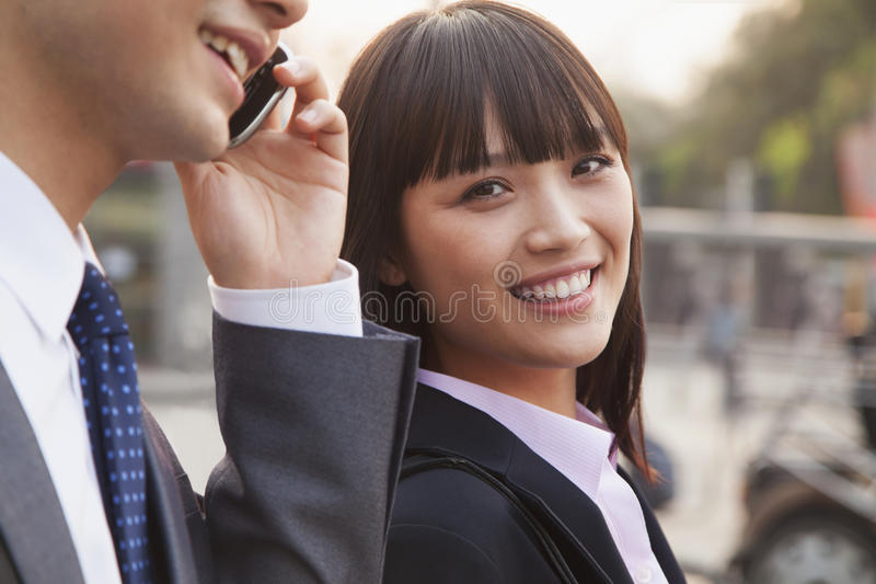 Two young business people outside on the street using phone in Beijing, portrait stock photos