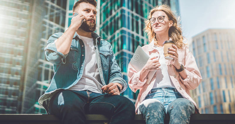 Two young business people are sitting on street. Hipster guy is talking on cell phone, girl is drinking coffee stock images