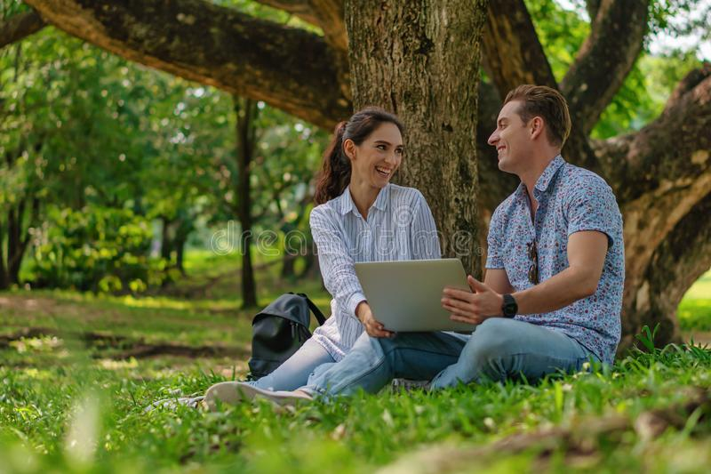 Two young business people sitting together under tree working with laptop computer together in park stock photo