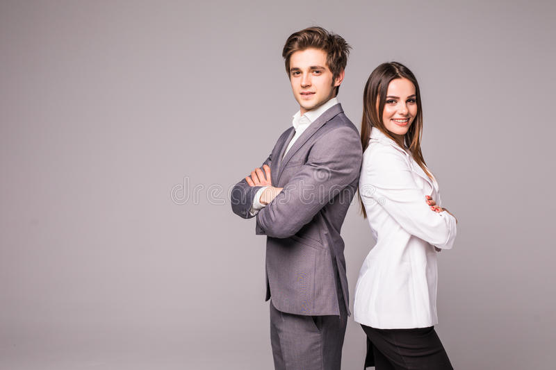 Full length of two young business people standing back to back with hands crossed isolated on grey background stock photography