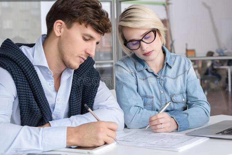 Two Young Business People Working in Office royalty free stock images