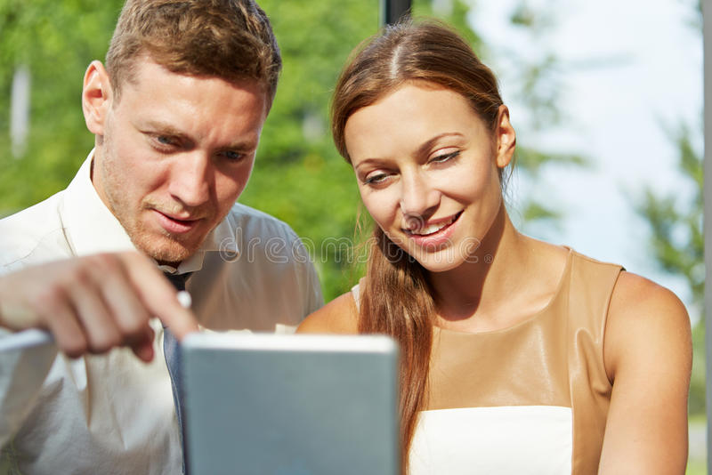 Two young business people working with tablet computer stock photography
