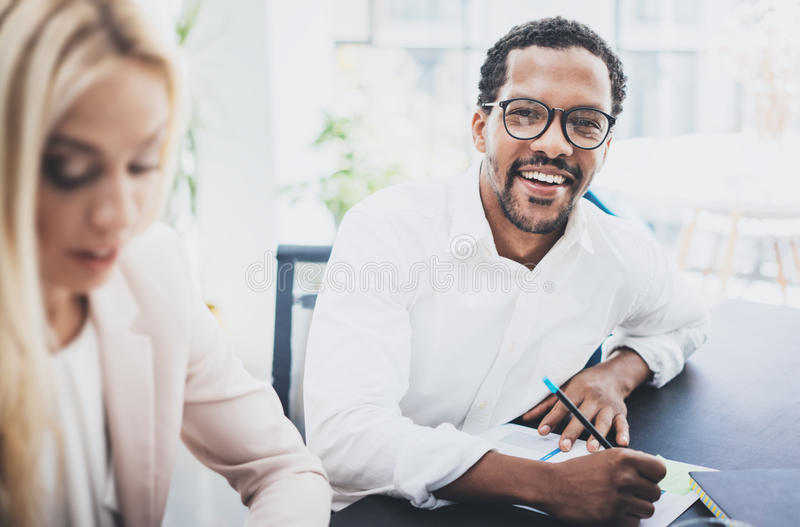 Two young business people working together in a modern office.Black man wearing glasses, looking at the camera and stock photography