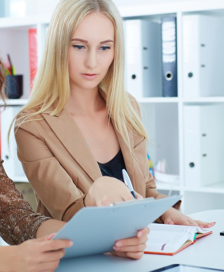 Two young business woman or office workers discussing paperwork sitting in office background. royalty free stock photography
