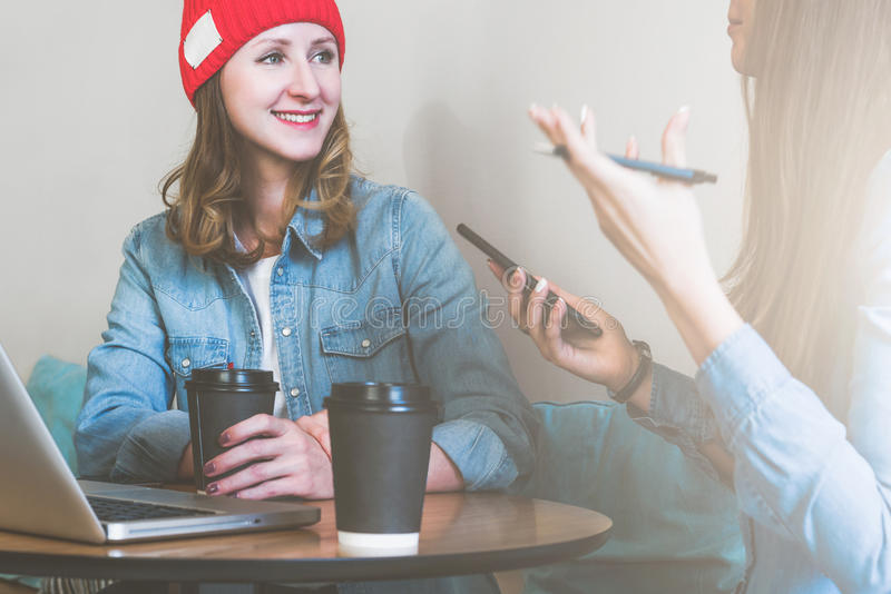 Two young business women sitting at table in cafe, drinking coffee and talking. First woman holding pen and smartphone. Two young business women sitting at royalty free stock photography