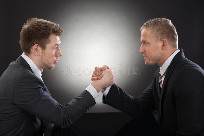 Two young businessman arm wrestling. Close-up Of Two Young Businessman Competing In Arm Wrestling royalty free stock photo