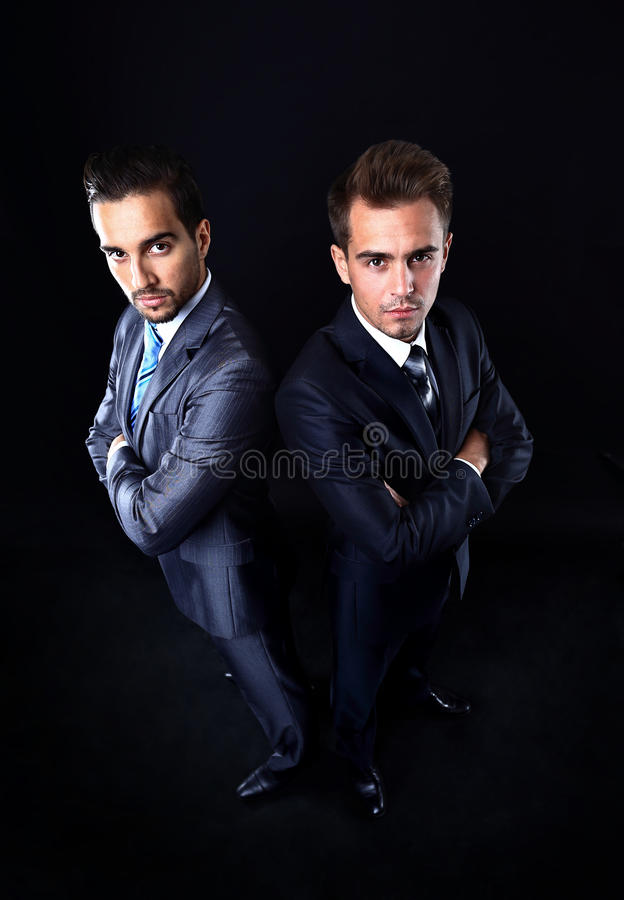 Two young businessmen full body. Isolated on black stock photos