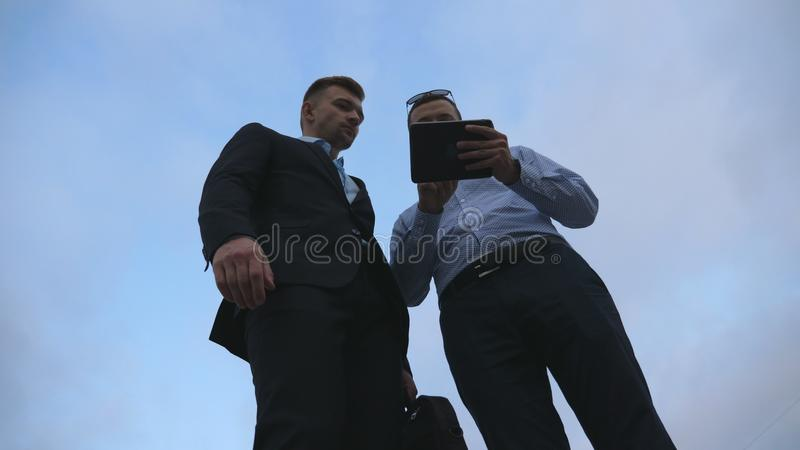 Two young businessmen meet, shake hands and talking outdoor. Business men using tablet pc outside with sky at background royalty free stock photos