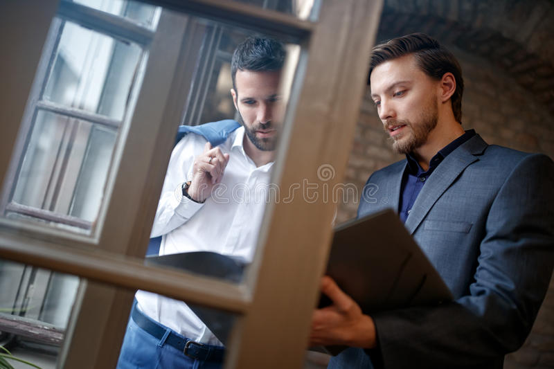Two young businessmen in office reading business plan royalty free stock images
