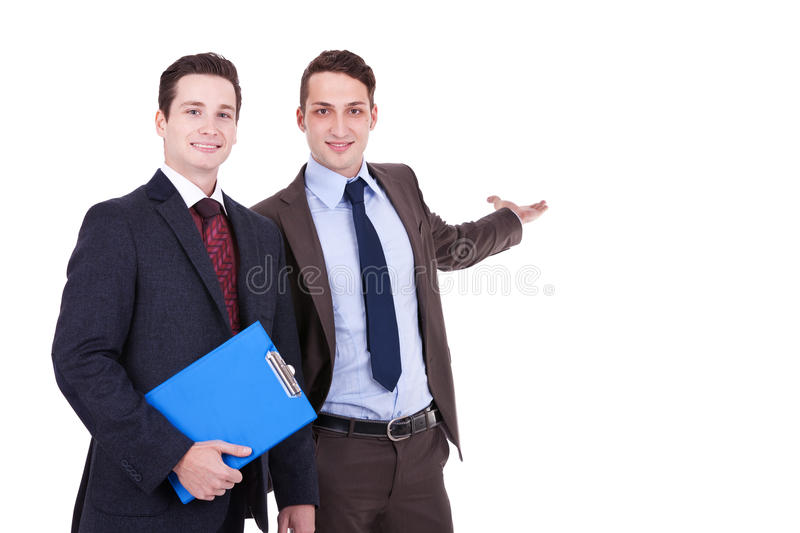 Two young businessmen presenting. Something on white background stock images