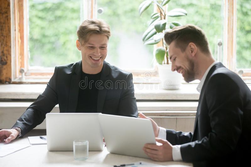 Two young businessmen using laptops talking discussing at office royalty free stock photos