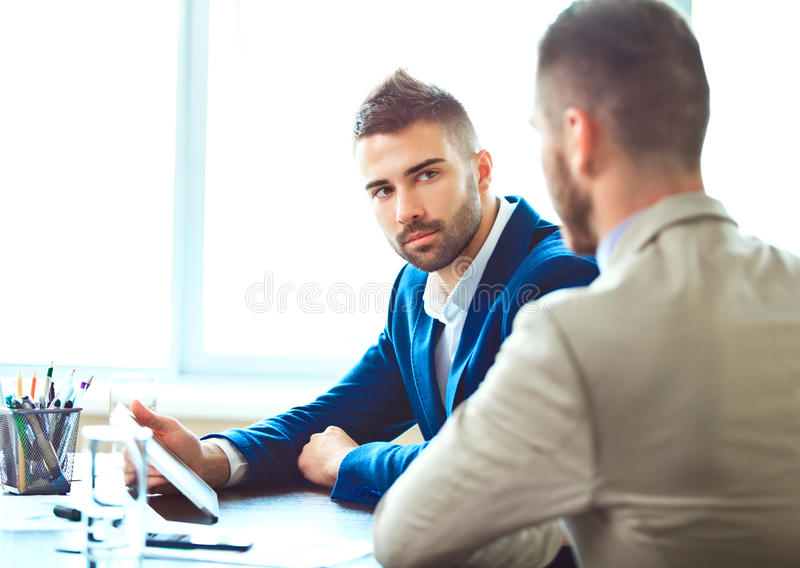 Two young businessmen using touchpad at meeting. Image of two young businessmen using touchpad at meeting stock photo