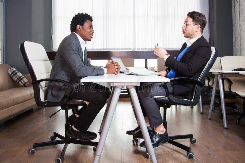 Two young businessmen, white desk, job interview, teamwork royalty free stock image
