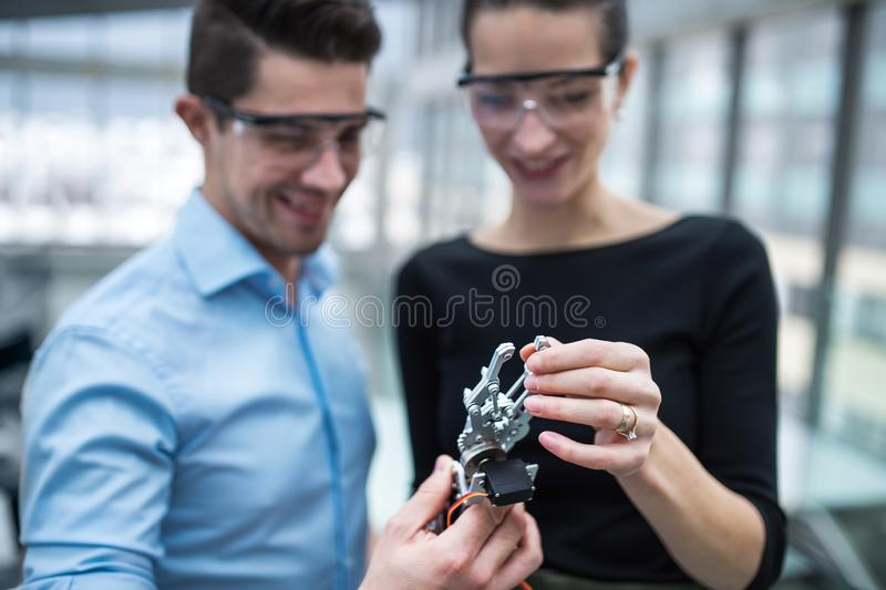 Two young businesspeople or scientists with robotic hand standing in office, talking. stock photography