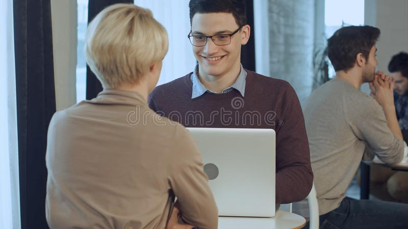 Two young businesspeople using laptop in lobby of modern office royalty free stock photo
