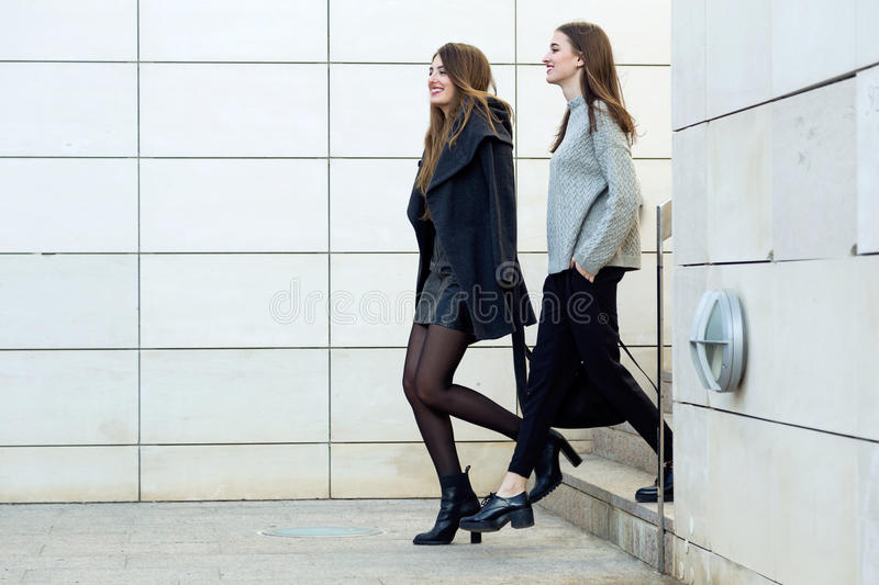 Two young businesswoman walking on the street near office building. royalty free stock photography