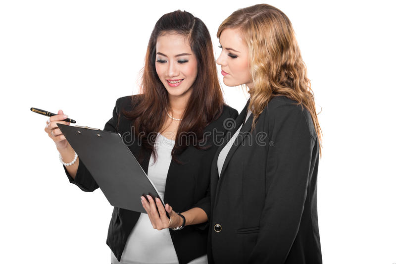 Two young businesswoman wtih a clipboard, isolated stock images