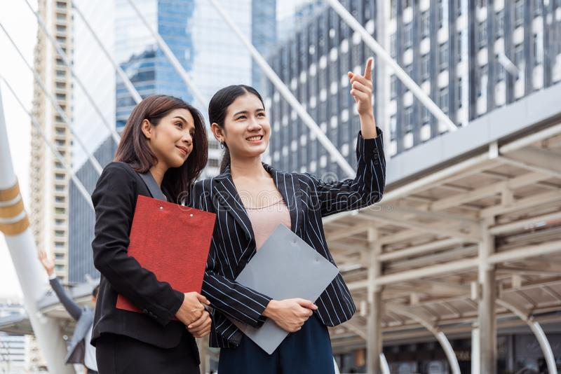 Two young businesswomen looking and pointing forward for thinking of future plan and sale break even point after marketing. stock photography