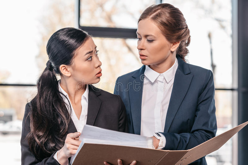 Two young businesswomen working together with folder and looking at each other. Business team working concept stock photo