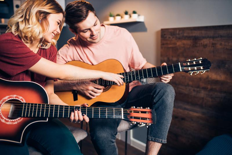 Two young caucasian people relax spending time together, playing guitar royalty free stock photo
