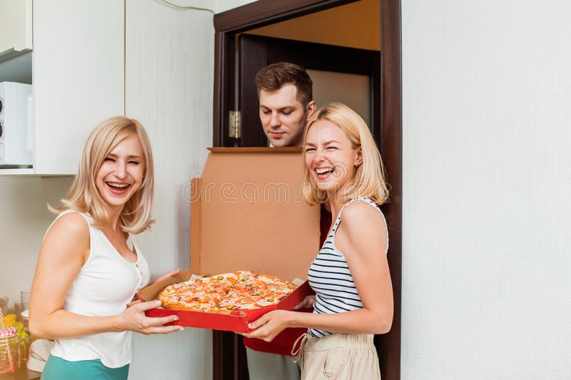 Two young caucasian woman receiving pizza from delivery man at home. Courier delivering pizza to clients home. Two happy joyful young women satisfied with the stock images