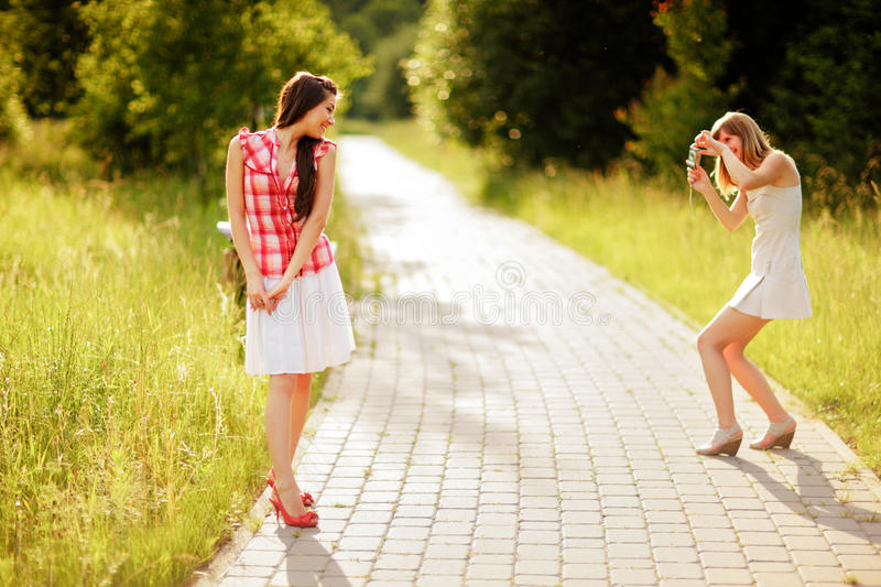 Two young caucasian women photographing themselves on small digital camera. royalty free stock photography