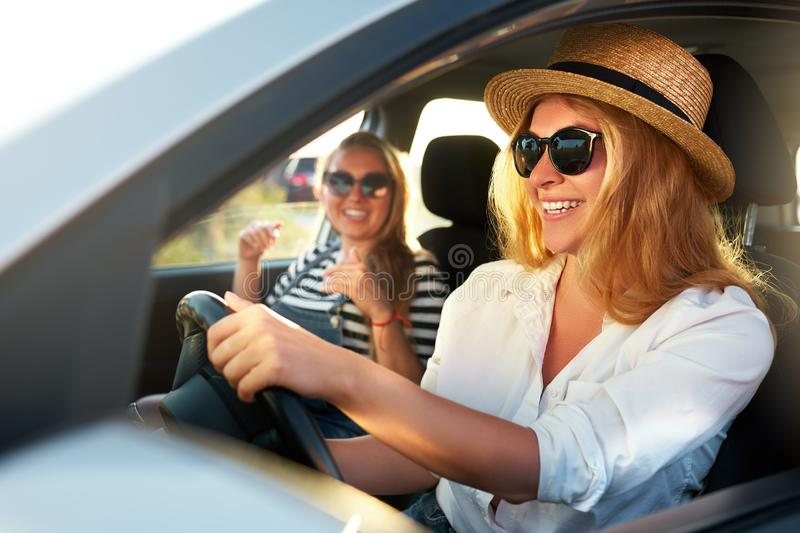 Two young cheerful smiling women in a car on vacation trip to the sea beach. Girl in glasses driving a vehicle from royalty free stock photos